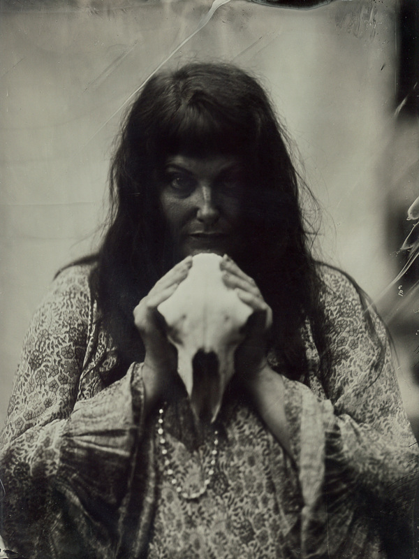 Black and white photograph of a woman holding a sheep skull taken with an antique camera.
